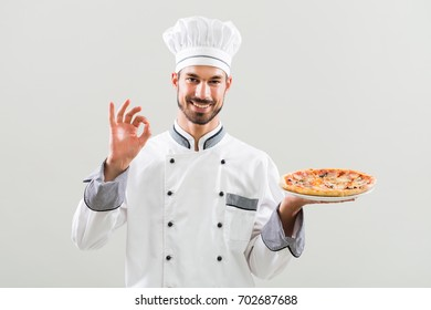 Smiling chef is holding pizza and showing ok sign on gray background.Chef with pizza gesturing