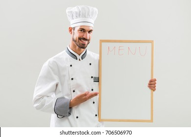 Smiling chef holding  whiteboard on gray background.Chef menu suggestion
