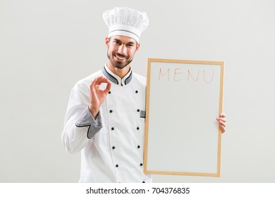 Smiling chef holding whiteboard and showing ok sign on gray background.Chef menu suggestion
