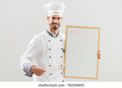 Smiling chef holding wooden spoon and whiteboard on gray background.Chef menu suggestion