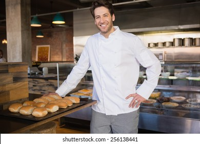 Smiling chef leaning on counter at the bakery