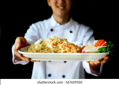 Smiling Chef proudly presenting crab fried rice in dark dramatic background