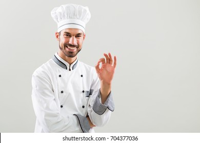 Smiling chef is showing ok sign on gray background.Chef gesturing