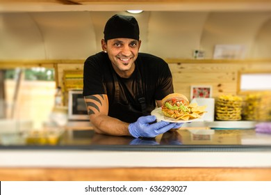 Smiling chef in uniform looking at camera while holding plate with served burger.