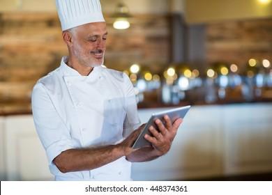 Smiling chef using digital tablet in restaurant