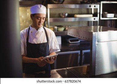Smiling chef using digital tablet in the commercial kitchen