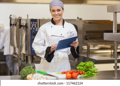 Smiling chef using her digital tablet in the kitchen beside the vegeatables