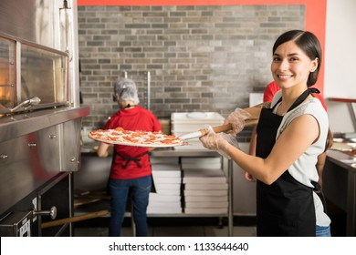 Smiling chef wearing uniform putting raw pizza in modern oven for baking while looking at camera and staff working in background in pizza shop