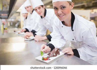 Smiling Chef's finishing dessert plates in the kitchen