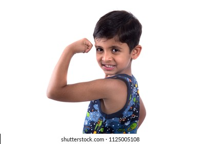 smiling child boy showing his hand biceps muscles strength on white background.