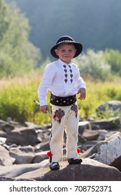 Smiling child boy in traditional Polish mountain outfit and black hat stands on mountain rocks. Vertical full body portrait
