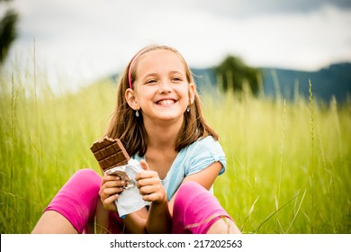 Smiling child eating and relishing chocolate - outdoor in nature
