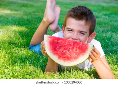 Smiling child eating watermelon lying on grass outdoors in summer