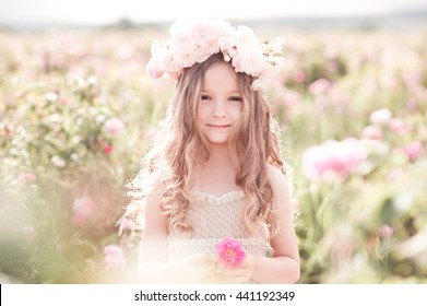 Smiling child girl 4-5 year old holding rose flower in meadow outdoors. Looking at camera. Childhood.