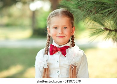 Smiling child girl 6-7 year old posing outdoors. Wearing white shirt with red bow tie. Back to school. Childhood.