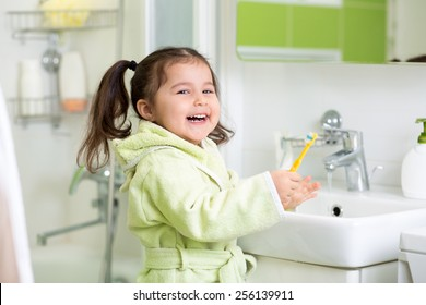 Smiling child girl brushing teeth in bath