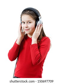 A smiling child girl listens to music through headphones on the white background