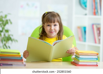 smiling child girl with opened book at table