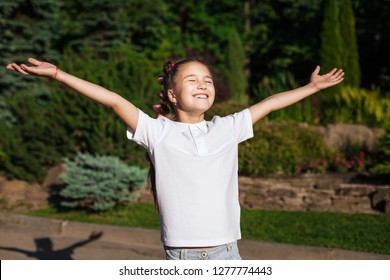 smiling child girl with pigtails waving on the wind wearing white shirt spreading hands in a sunny summer park. pine trees on a background