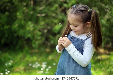 A smiling child holds a flower