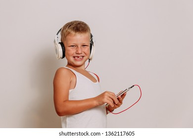 smiling child in large white headphones on a white background. toothless boy