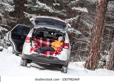 Smiling child laying inside of car back boot for luggage. Winter evergreen forest with huge snow covered pines