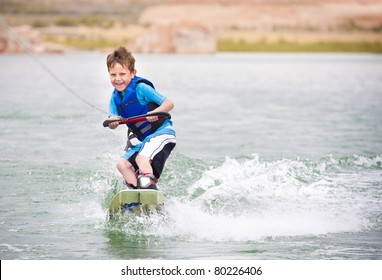Smiling Child learning to wake-board