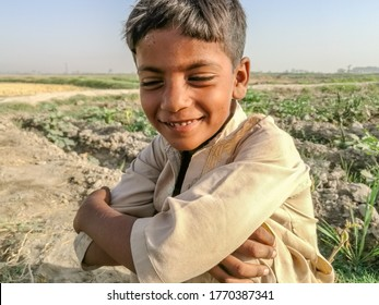 smiling child sitting in the fields