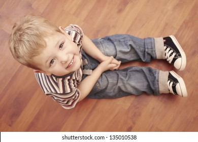 smiling child sitting oh the floor