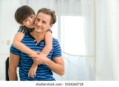 Smiling child and their father are very happy, they are at home