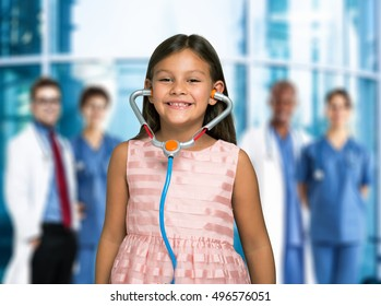 Smiling child using a toy stethoscope in front of a group of doctors