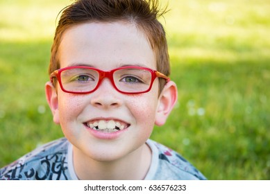 Smiling child wearing red glasses