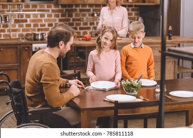 smiling children with disabled father in wheelchair serving table for dinner at home