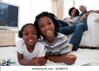 Smiling children drawing lying on the floor in the living room