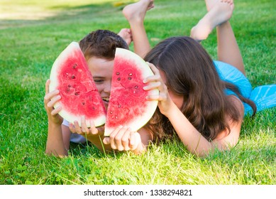 Smiling children eating watermelon on grass outdoors in summer
