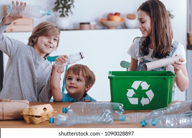 Smiling children having fun while segregating plastic bottles and paper into a green bin