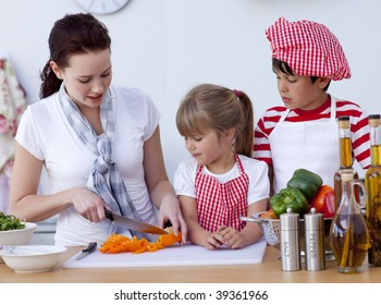 Smiling children helping mother cooking in the kitchen