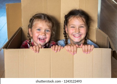 Smiling children look out of a large cardboard box. Moving to a new home concept. Happy family relocation. Family unpacks, children play with boxes. Children have fun and enjoy playing hide and seek.