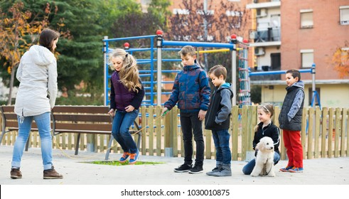smiling children playing rubber band jumping game and laughing outdoors