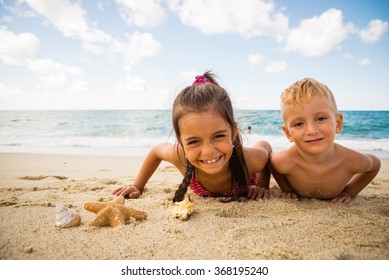smiling children plays with a starfish on the beach on a summer day