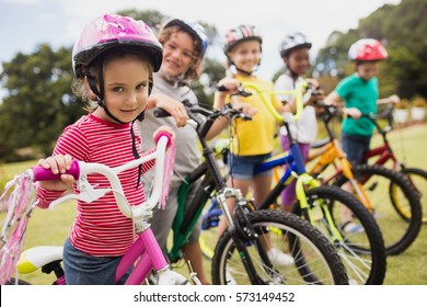 Smiling children posing in raw with bikes in the park