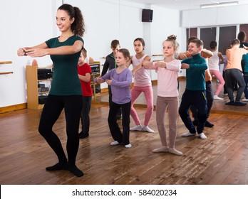 smiling children primary school age rehearsing ballet dance in studio