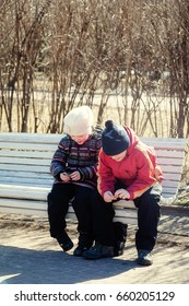 Smiling children are sitting on a Park bench