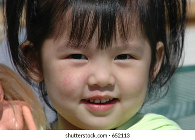 Smiling Chinese girl with doll