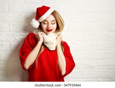 Smiling Christmas Girl With Closed Eyes In Red Winter Clothes At White Brick Wall Background