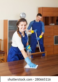Smiling cleaners cleaning furniture and floor in room