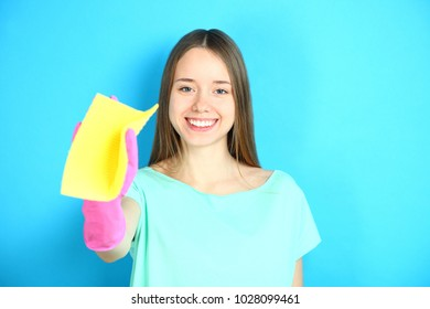 A smiling cleaning lady in rubber gloves with a viscose napkin on a blue background.