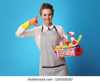smiling cleaning woman in apron with a basket with detergents and brushes showing call me gesture isolated on blue. One call and dedicated service specialists will provide the best customer service