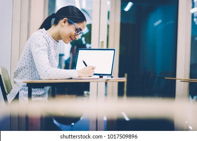Smiling clever female student writing report sitting at desk in college classroom nra laptop with blank screen,skilled woman enjoying learning information and making notes on language courses