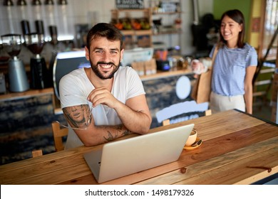 Smiling coffee seller owner in coffee shop working on laptop.